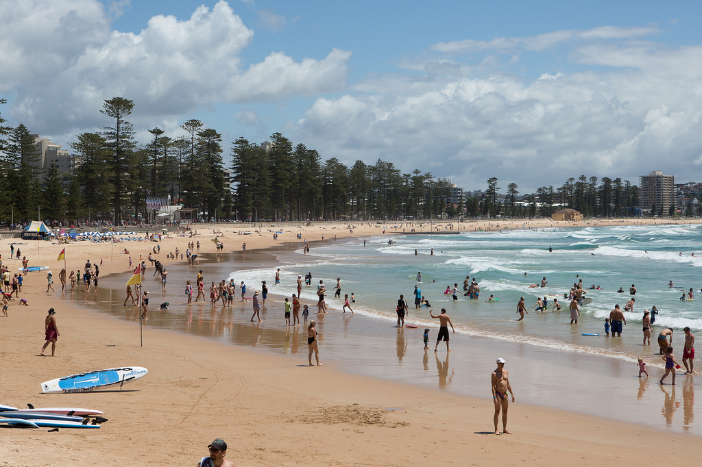 Tourists and Sydneysiders enjoy the waves at Manly Beach